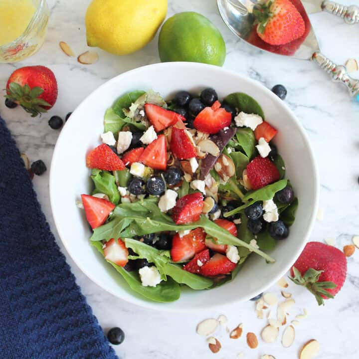 Overhead of Mixed Berry Salad in white bowl with fruit and nuts scattered around.