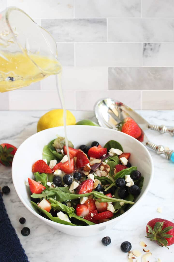 Pouring dressing over salad on marble table.