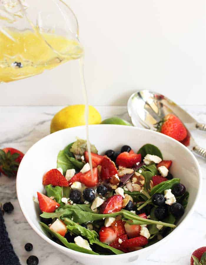 pouring vinaigrette on berry salad