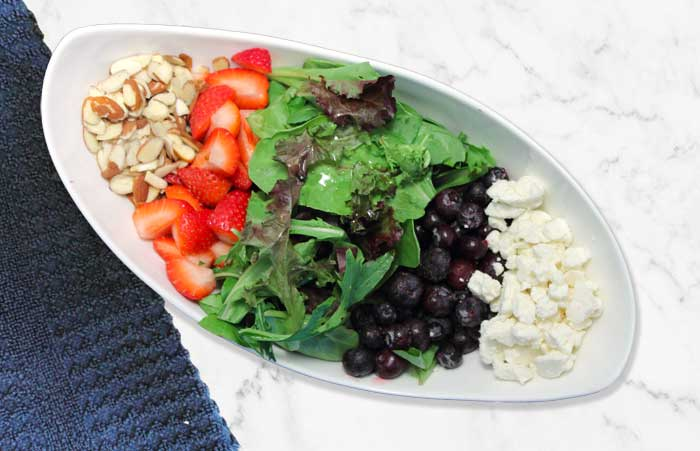 Deconstructed berry salad with rows of almonds, strawberries, greens, blueberries and feta in white bowl