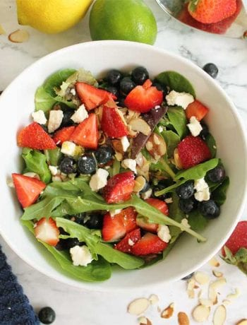 overhead of summer salad in white bowl with lemon, lime and berries around it