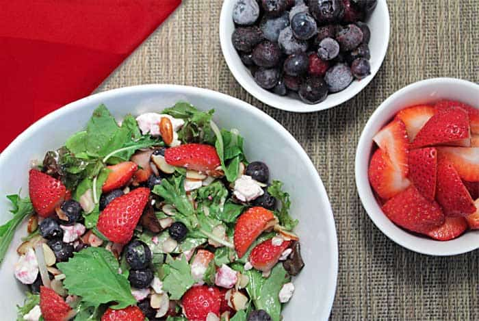 Summer Salad in white bowl with smaller bowls of strawberries and blueberries beside it
