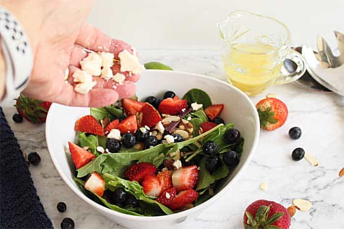sprinkling feta over summer strawberry salad