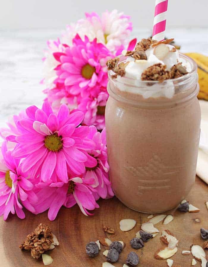Healthy smoothie ready for breakfast , topped with whipped cream, with granola and almonds on top and flowers beside it.