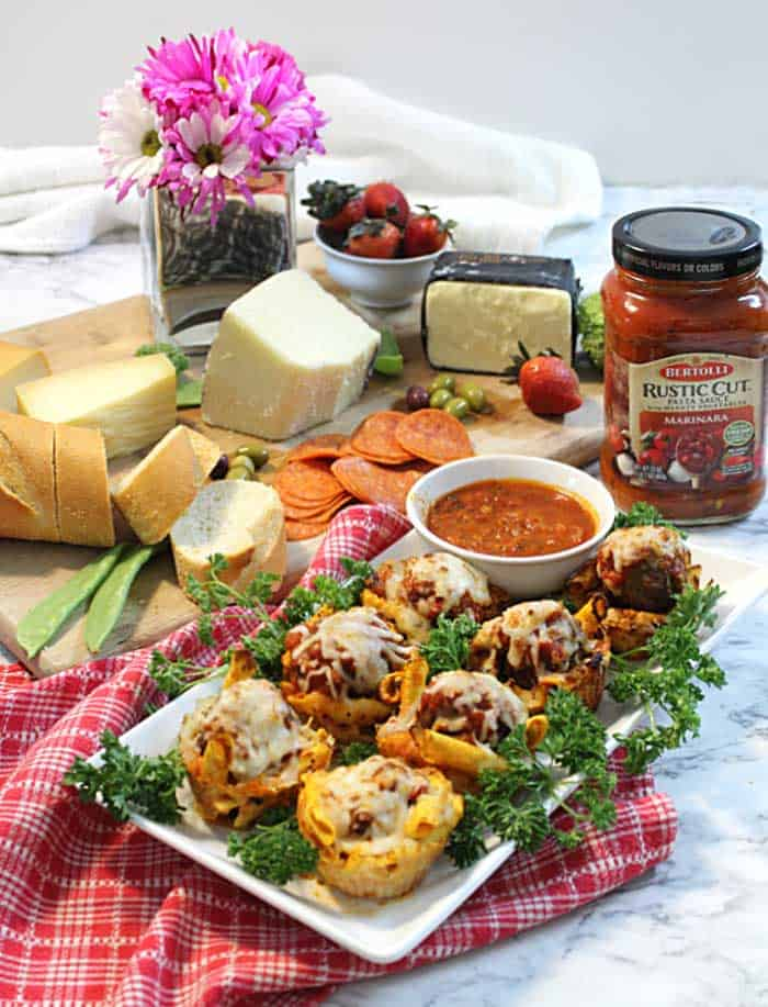 Appetizer spread with cheese board and pasta muffins.