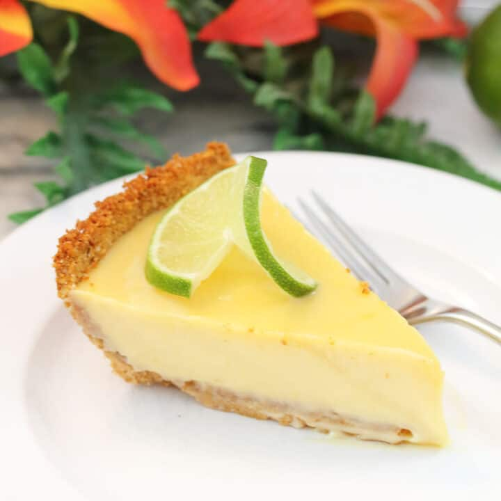 Slice of key lime pie on white plate in front of flowers.