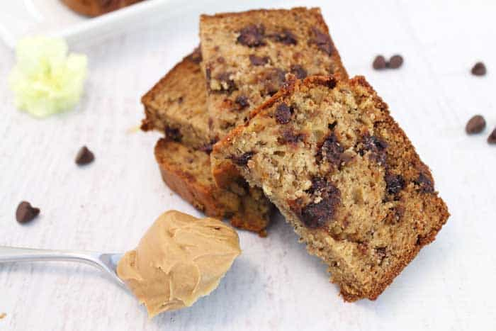 Slices of chocolate chip banana bread with spoonful of peanut butter on white table.