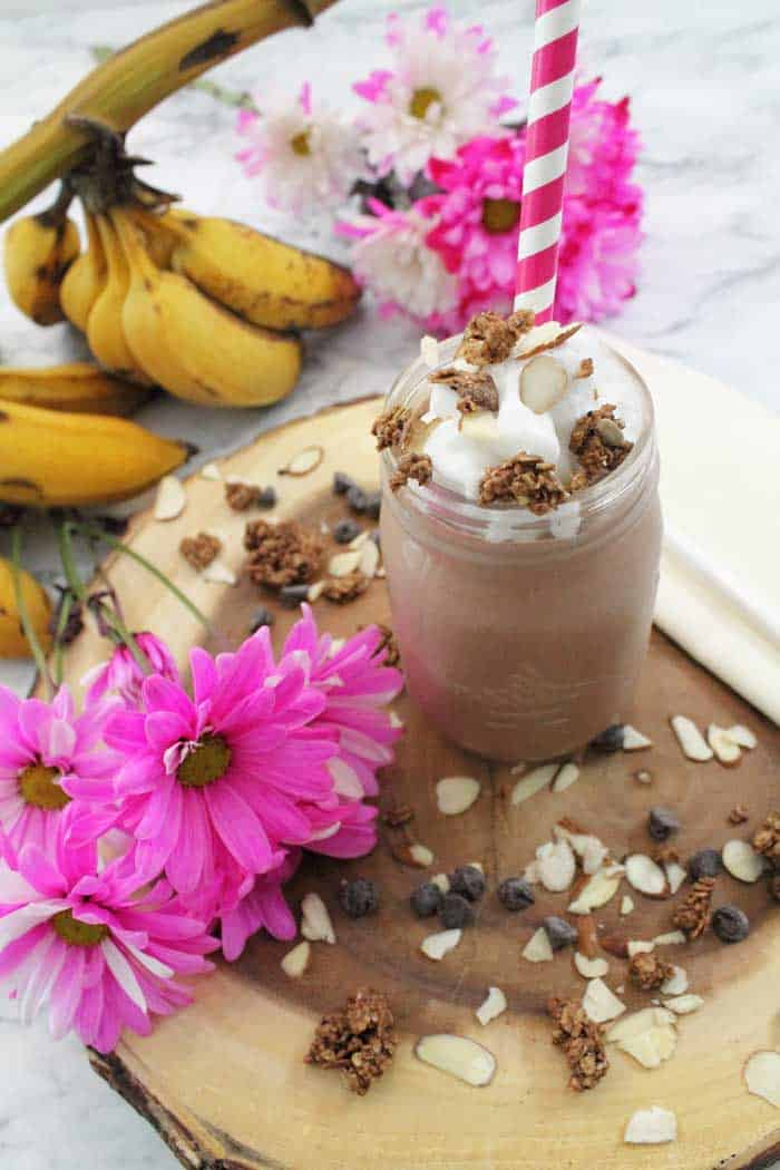 Topped smoothie in mason jar with red striped straw and bananas in back, pink flowers on side.