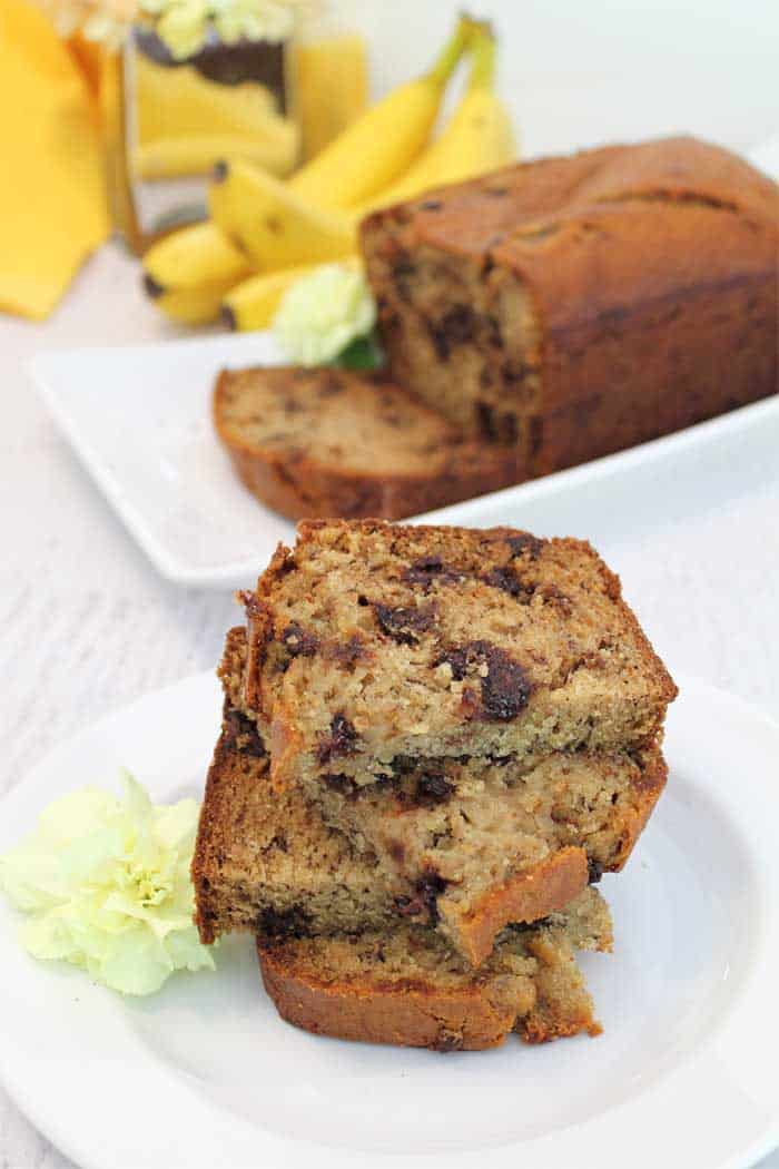 Stacked slices of chocolate chip banana bread with loaf of bread and banana in background.