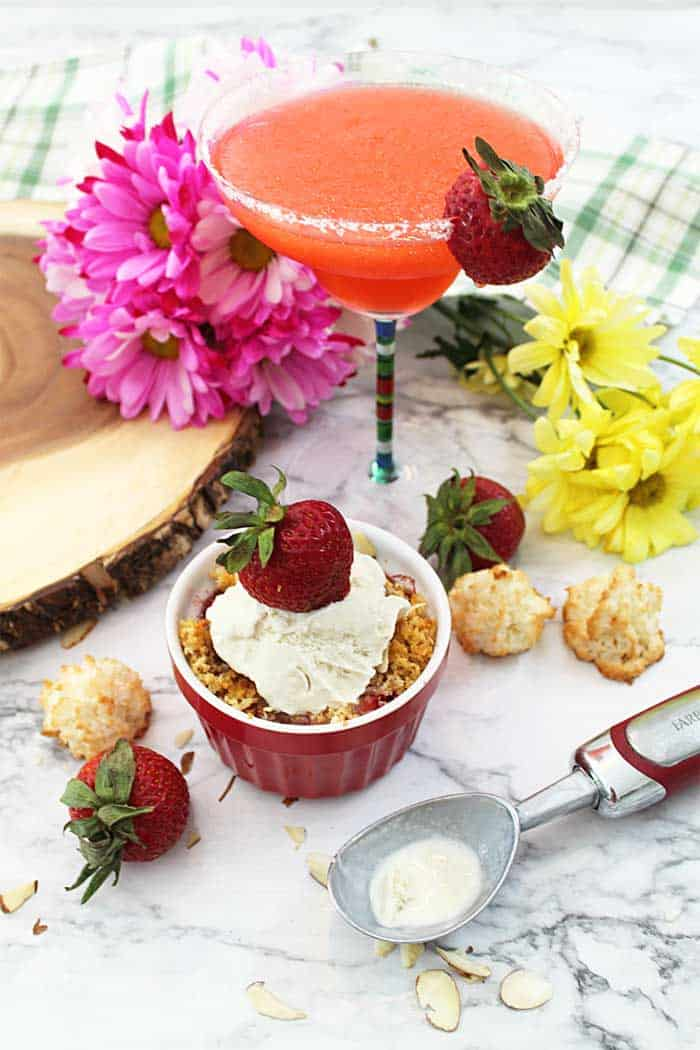 Strawberry Crisp on white tabe with margarita & flowers in background.