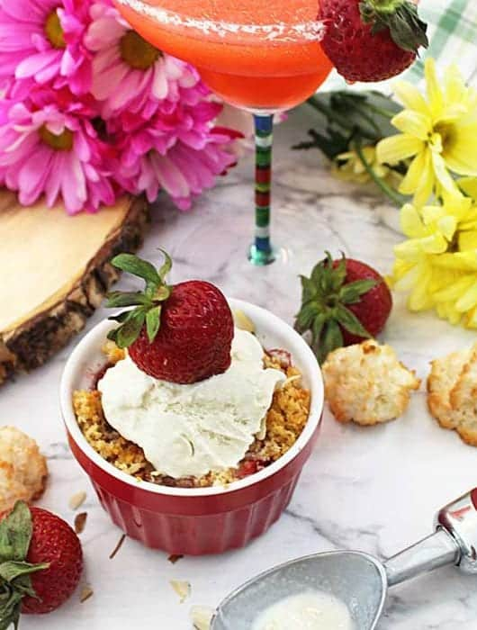 Strawberry Crisp with ice cream on white table with margarita in background.