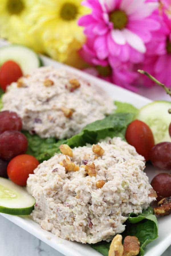 Closeup of mounded chicken salad on white platter with grapes and cucumber slices.