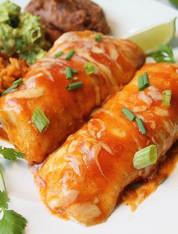 Closeup of enchiladas on white plate with lime slice rice guacamole and beans.