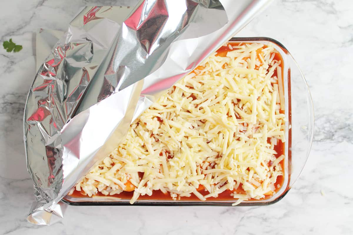 Covering enchiladas with foil to bake.