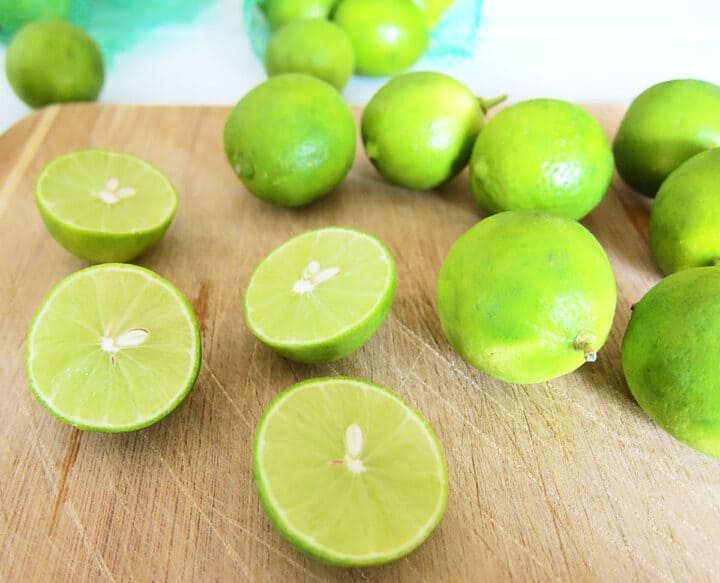 Key limes on wooden cutting board.