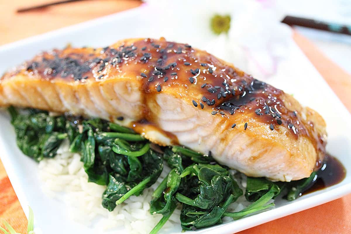Closeup of plated Asian baked salmon over spinach on white plate.