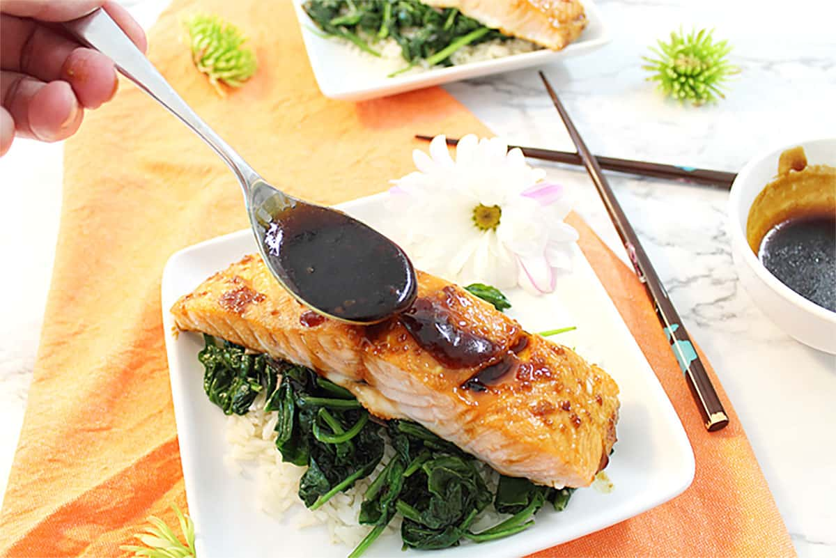 Drizzling maple glaze on baked salmon.