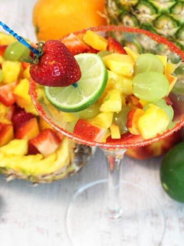 single fruit cocktail in martini glass with lime and strawberry garnish.