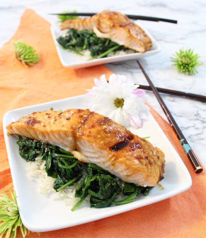 Salmon dinner for 2 on white plates with white dairy on plate.