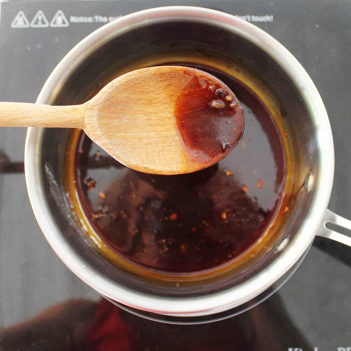 Closeup of thickened maple sauce on wooden spoon.