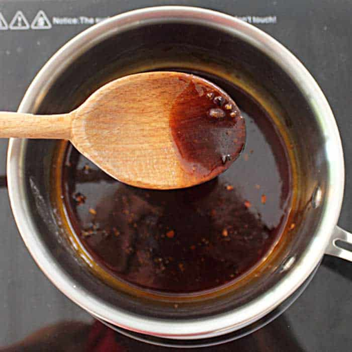 A spoon holding maple glaze to show how it has thickened.