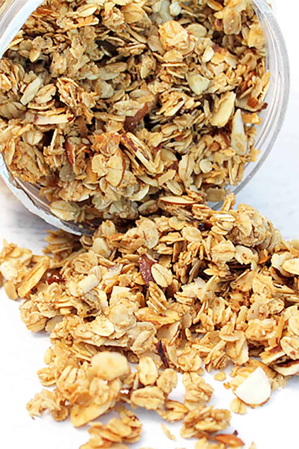 Granola spilling out of container onto white table.