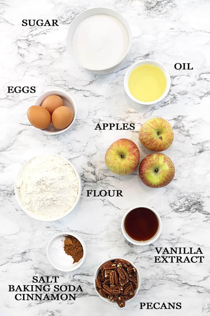 Apple cake ingredients on marble table.
