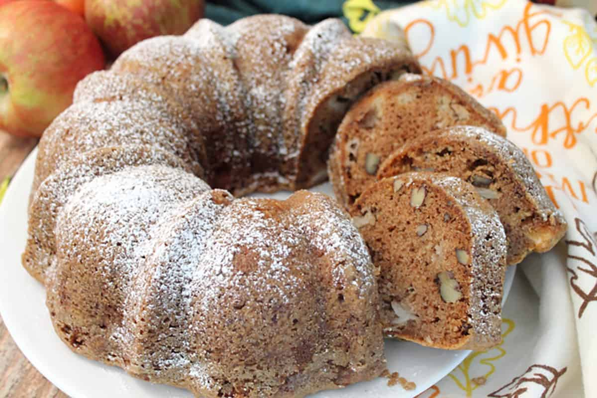 Closeup of sliced apple cake with apples and fall towel around it.