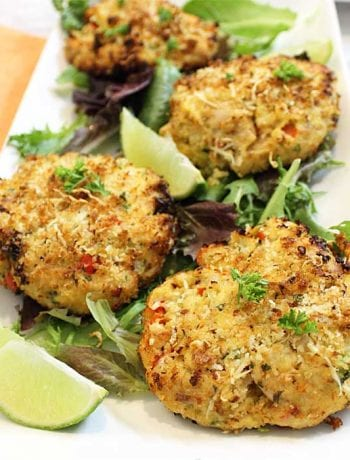 Closeup of cooked tuna fish cakes on white plate.