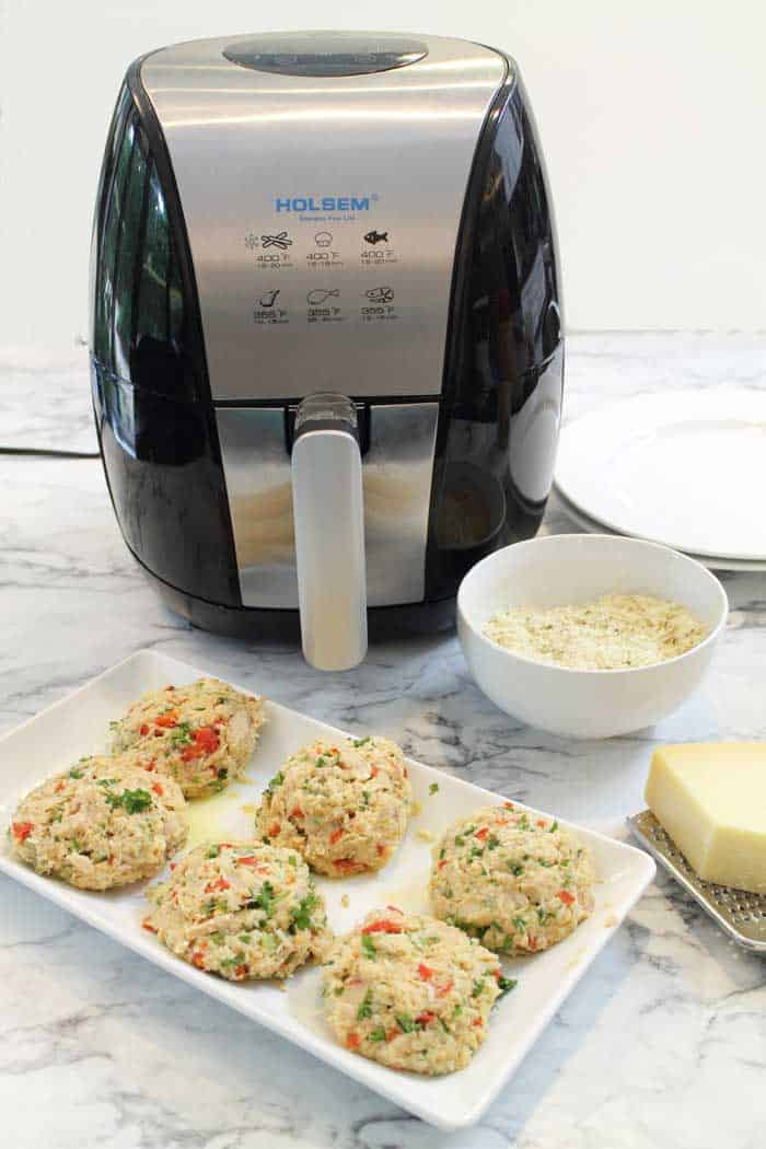 Uncooked tuna fish cakes in front of air fryer and ready for crumbs.