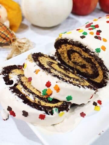 closeup of Chocolate Pumpkin Swiss Cake Roll on white plate.
