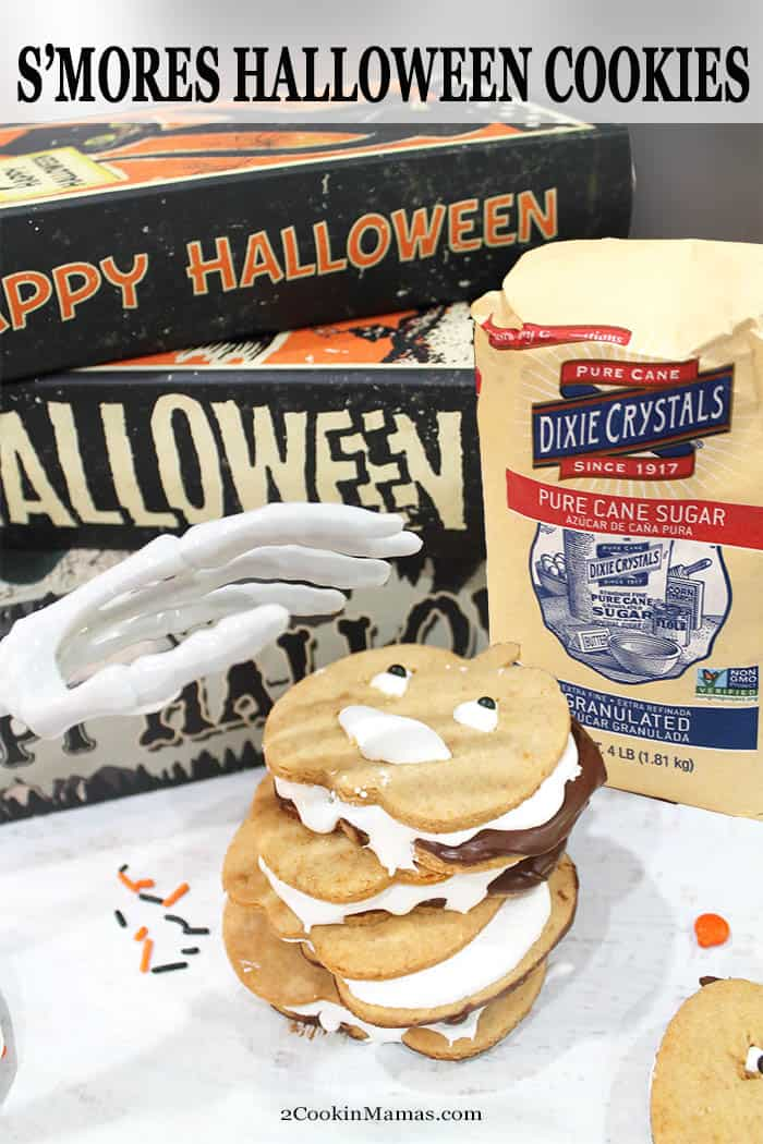 #AD Everyone loves s\'mores and these pumpkin-shaped Halloween s\'mores cookies have all the flavors in one fun-to-make cookie. Crispy graham cookies are coated with chocolate and sandwiched with marshmallow fluff for one yummy ooey gooey cookie. Let the kids decorate them with eyes for an extra spooky look. Once you take a bite, you\'ll be licking your fingers and reaching for more! #cookies #smores #halloween #chocolate #marshmallows #grahamcracker #easy #recipe #withfluff #sandwich