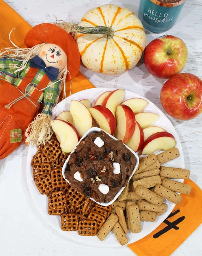 overhead of dip with dippers of apples grahams and pretzels.