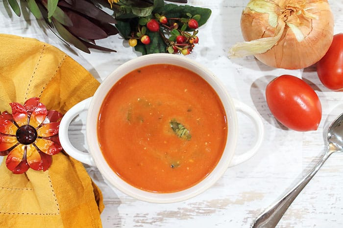 Tomato Basil Soup in white bowl with gold napkin.