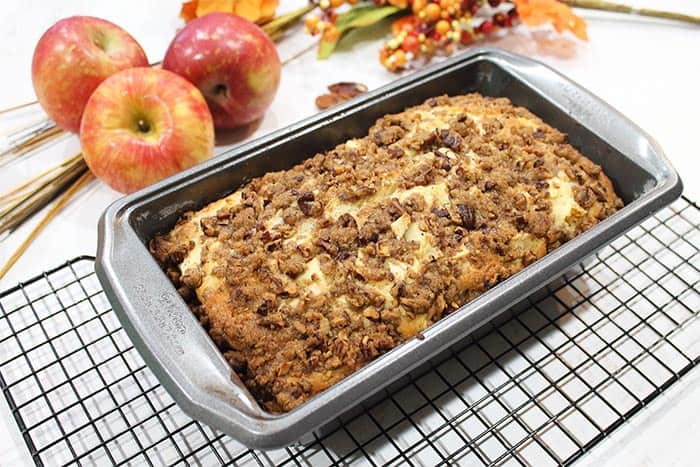 Baked cinnamon apple bread in loaf pan, cooling on wire rack.