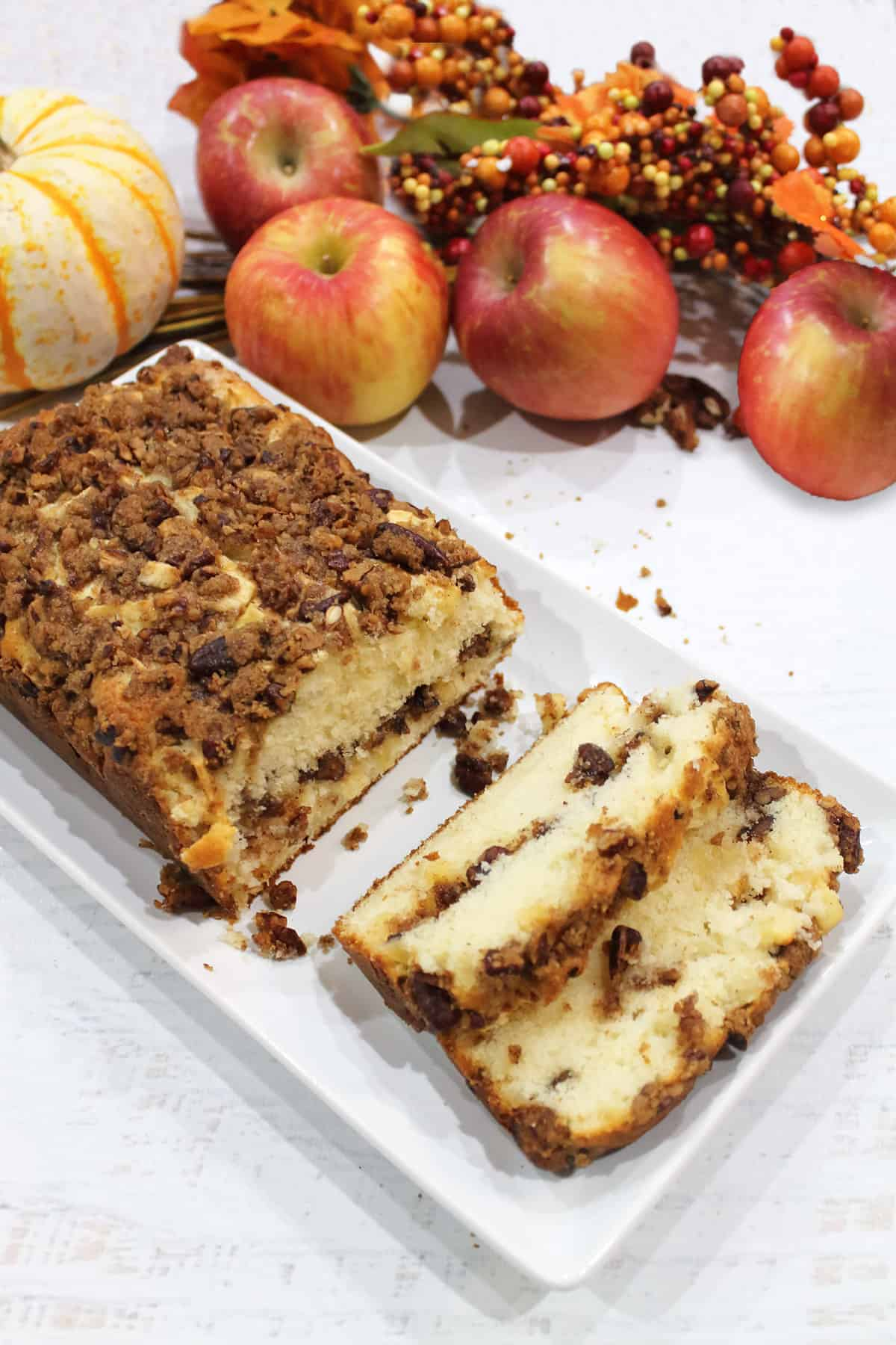 Cinnamon Apple Streusel Bread sliced on white platter with fall apples and pumpkin in back.