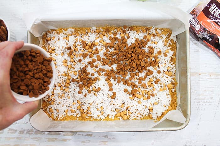 Sprinkling cinnamon chips over coconut layer.