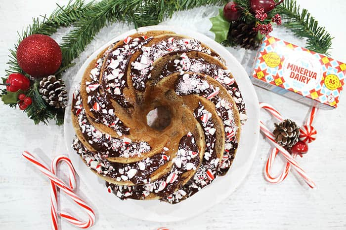 Decorated bundt cake on white plate with Minerva butter on side