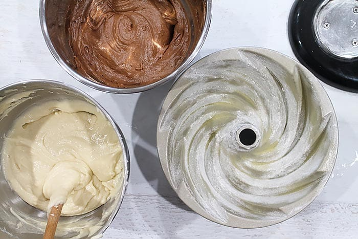 Peppermint and chocolate batters beside greased and floured bundt pan.