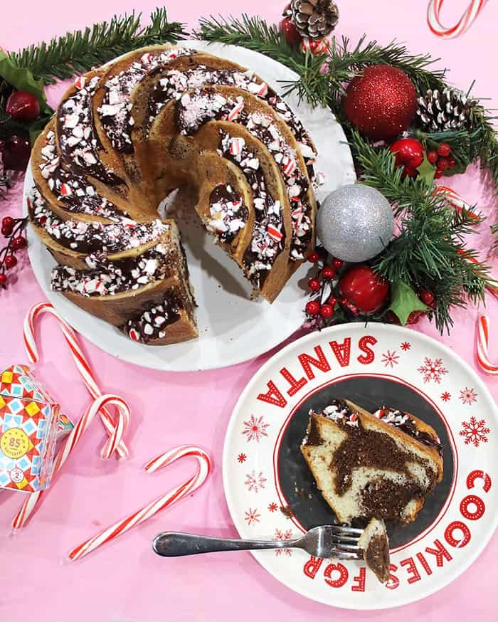 Sliced cake with piece of cake with a bite on fork on Santa plate.