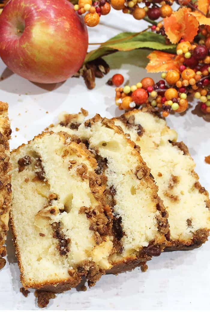 Sliced cinnamon apple bread showing streusel filling on white table.
