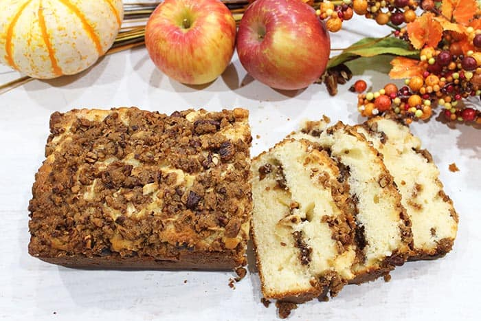 Sliced cinnamon apple bread showing loaf and slices with fall fruit in background.