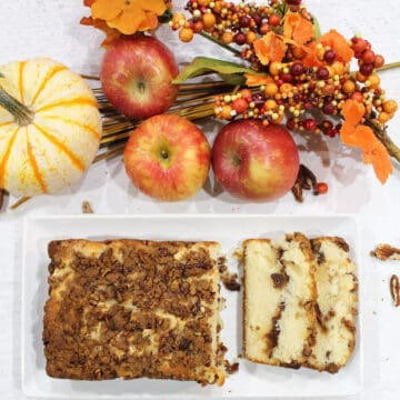 Overhead of sliced bread with fall leaves, berries and apples in back.