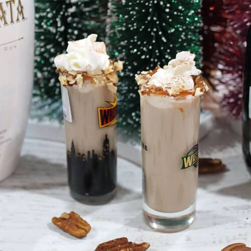 2 pecan pie shots with Rum Chata and Chrsitmas trees in background