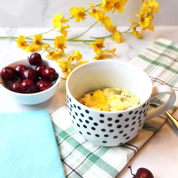 Baked sausage scramble in white polka dot mugs with cherries and yellow flowers.