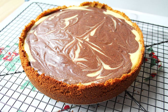 Closeup of baked chocolate swirl cheesecake on cooling rack.