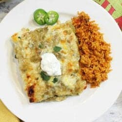 overhead of smothered green chile chicken burritos on white plate with spanish rice.