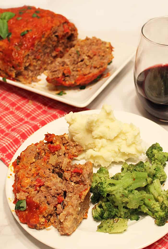 Slow Cooker Meatloaf dinner plated with wine.