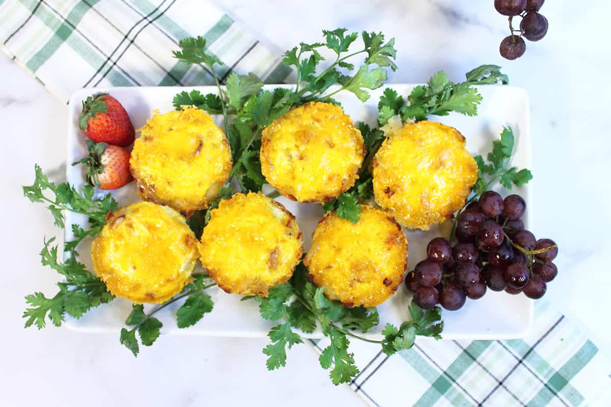 Overhead of hash brown cups with eggs on white platter with parsley and grapes.