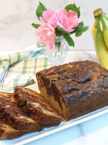 Banana bread on white platter with flowers and bunch of bananas.